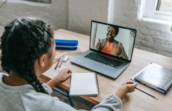 ethnic girl having video chat with teacher online on laptop